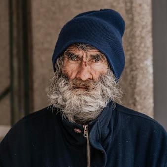 Vista frontal de um morador de rua com barba ao ar livre