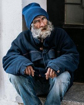 Vista frontal de um morador de rua com barba na porta