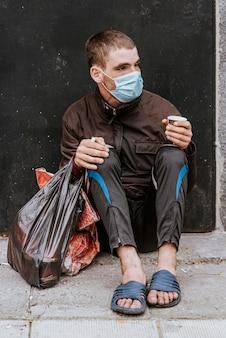 Vista frontal de um morador de rua com máscara médica ao ar livre e sacola plástica