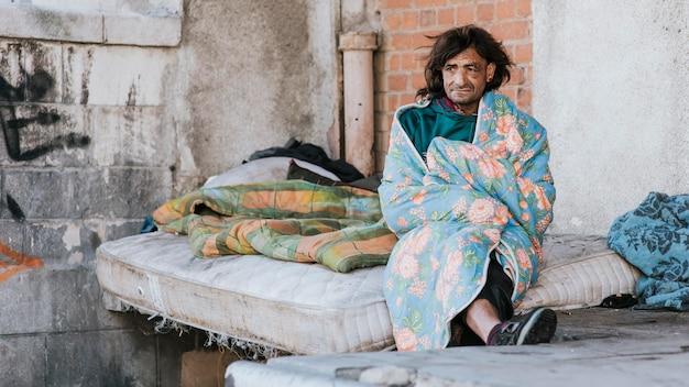 Vista frontal de um morador de rua no colchão sob o cobertor
