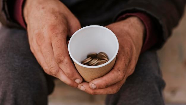 Vista frontal de um morador de rua segurando um copo com moedas