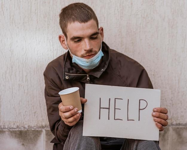 Vista frontal de um morador de rua segurando uma xícara e um cartaz de ajuda