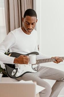 Vista frontal de um músico segurando uma guitarra elétrica e uma caneca