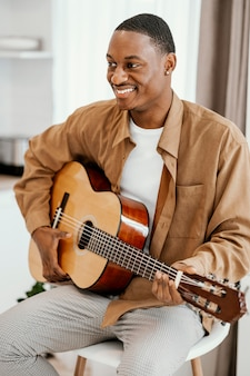 Vista frontal de um músico sorridente em casa tocando violão