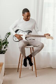 Vista frontal de um músico sorridente tocando guitarra elétrica em casa