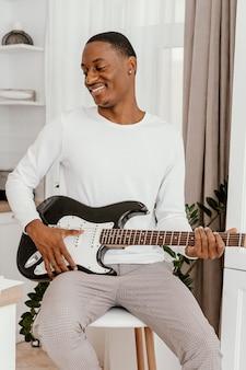Vista frontal de um músico sorridente tocando guitarra elétrica