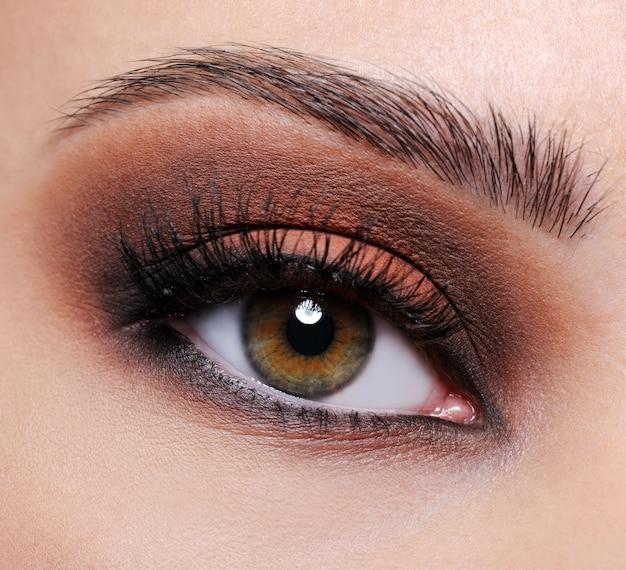 Vista frontal de um olho feminino em close-up com maquiagem de sombra marrom