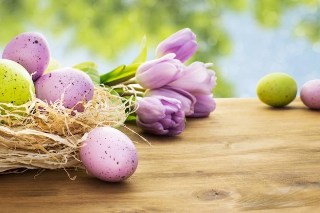 Vista frontal de um ovos de páscoa com tulipas roxas na madeira e fundo do céu de primavera.