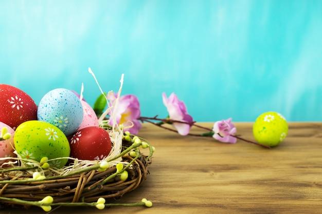 Vista frontal de um ovos de páscoa no ninho com ramos de flores da primavera em madeira marrom e turquesa fundo.