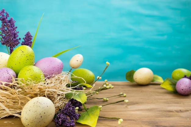 Vista frontal de um ovos de páscoa no ninho e primavera flores sobre fundo madeira e turquesa com espaço para mensagem.