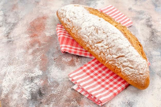Vista frontal de um pão em toalha de cozinha vermelha sobre fundo nu