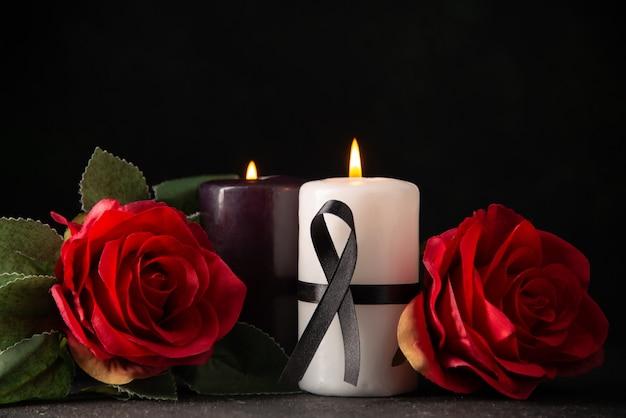 Vista frontal de um par de velas flores vermelhas sobre preto