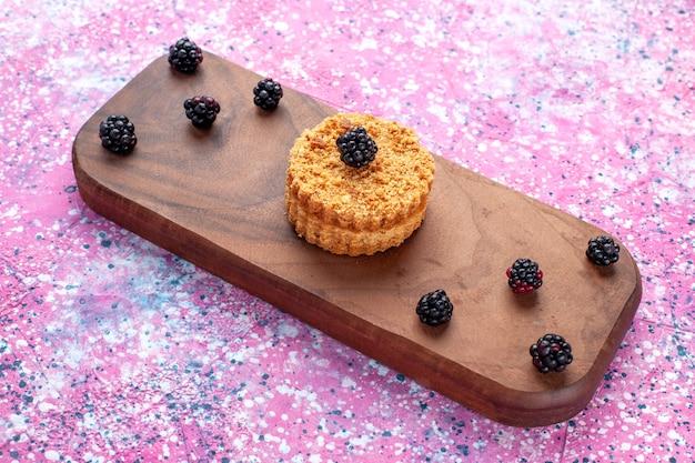 Vista frontal de um pequeno bolo com frutas na superfície rosa