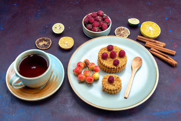 Vista frontal de um pequeno bolo redondo com framboesas frescas dentro do prato com chá de frutas e canela na superfície escura
