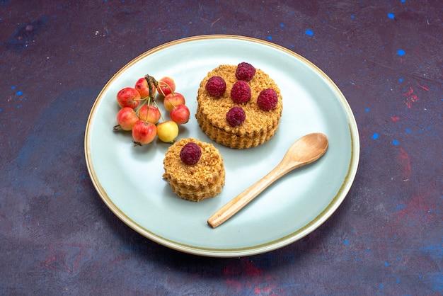 Vista frontal de um pequeno bolo redondo com framboesas frescas dentro do prato na superfície escura
