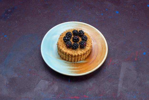 Vista frontal de um pequeno bolo redondo com frutas dentro do prato na superfície escura