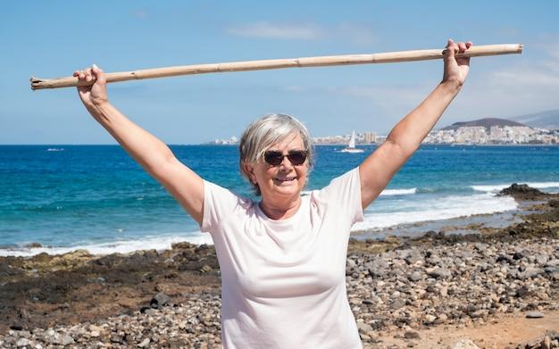 Vista frontal de um povo, mulher sênior, realizando alguns exercícios para os ombros na praia. horizonte na água. céu azul e mar ao fundo. férias ou pensão. serenidade e relaxamento