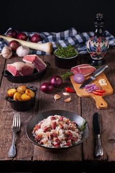 Vista frontal de um prato servido de arroz com carne seca em uma mesa de madeira rústica. placa de cozinha com pedaços de carne seca, cebola vermelha, alho, pimenta e uma faca de cozinha. fundo escuro com espaço de cópia