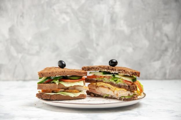 Vista frontal de um saboroso sanduíche com pão preto decorado com azeitonas em um prato em uma superfície branca manchada