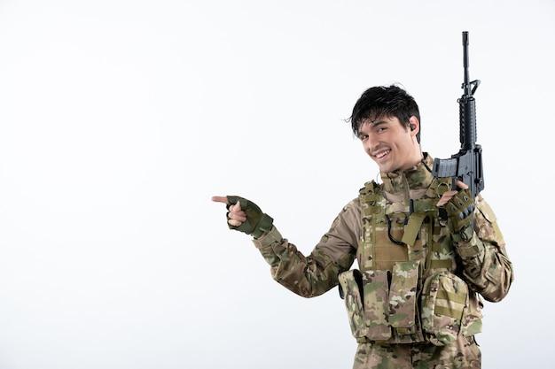 Vista frontal de um soldado com metralhadora na parede branca de camuflagem