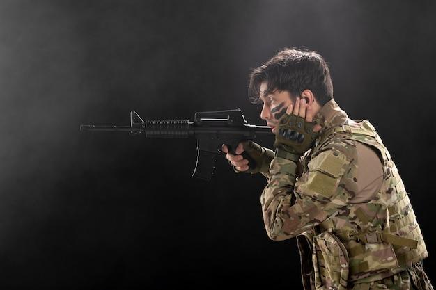 Vista frontal de um soldado lutando com um rifle em uma parede escura