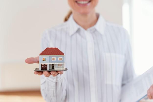 Vista frontal de um sorridente corretor de imóveis desfocado mostrando uma casa em miniatura