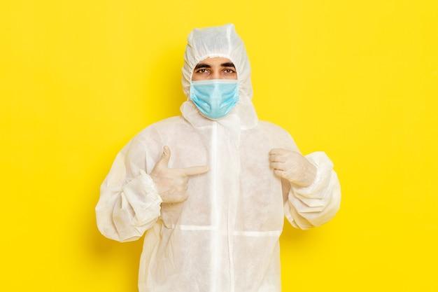 Vista frontal de um trabalhador científico do sexo masculino em traje de proteção especial e com máscara na parede amarelo-claro
