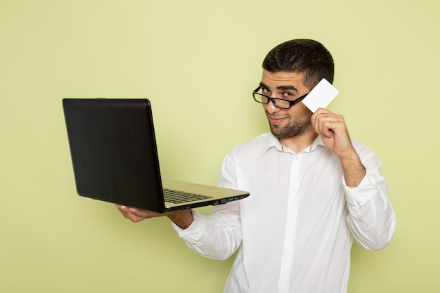 Vista frontal de um trabalhador de escritório com camisa branca, segurando e usando seu laptop na parede verde clara