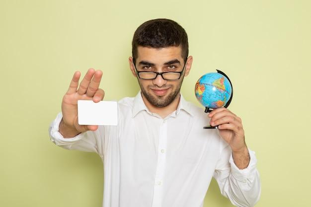 Vista frontal de um trabalhador de escritório com camisa branca segurando o globo e um cartão na parede verde-clara