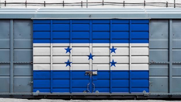 Vista frontal de um vagão de trem contêiner com uma fechadura de metal grande com a bandeira nacional de honduras. o conceito de exportação e importação, transporte, entrega nacional de mercadorias