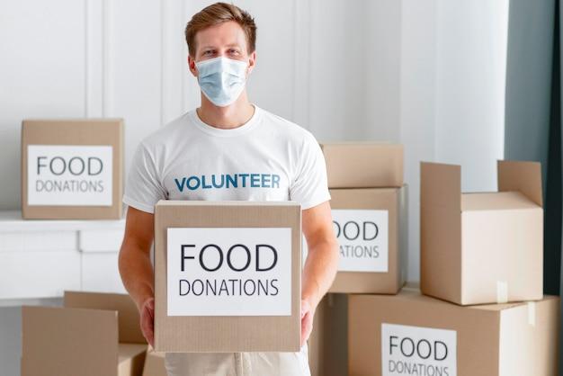 Vista frontal de um voluntário segurando uma caixa de doação de alimentos