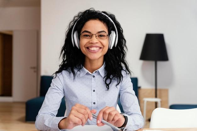 Vista frontal de uma adolescente sorridente em casa durante a escola online com fones de ouvido