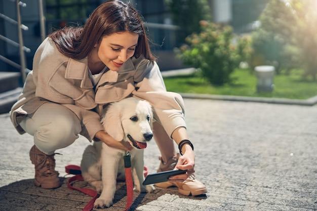 Vista frontal de uma adorável senhora e seu cachorro posando para a câmera do celular ao ar livre