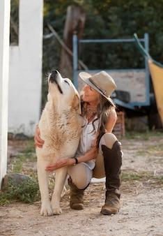Vista frontal de uma agricultora abraçando seu cachorro de fazenda