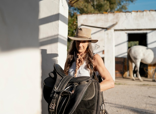 Vista frontal de uma agricultora carregando uma sela de cavalo