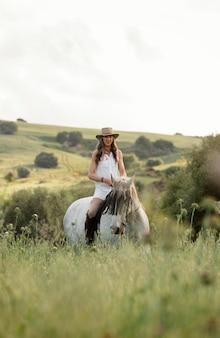 Vista frontal de uma agricultora cavalgando