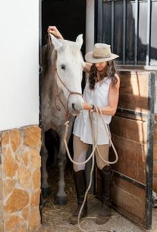 Vista frontal de uma agricultora com seu cavalo no rancho