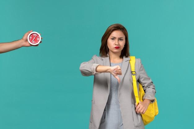 Vista frontal de uma aluna com uma jaqueta cinza e uma mochila amarela, mostrando uma placa diferente na parede azul clara