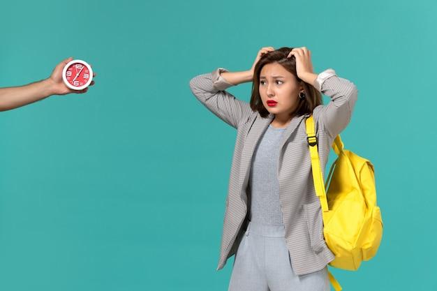 Vista frontal de uma aluna com uma jaqueta cinza e uma mochila amarela, posando com uma expressão confusa na parede azul clara