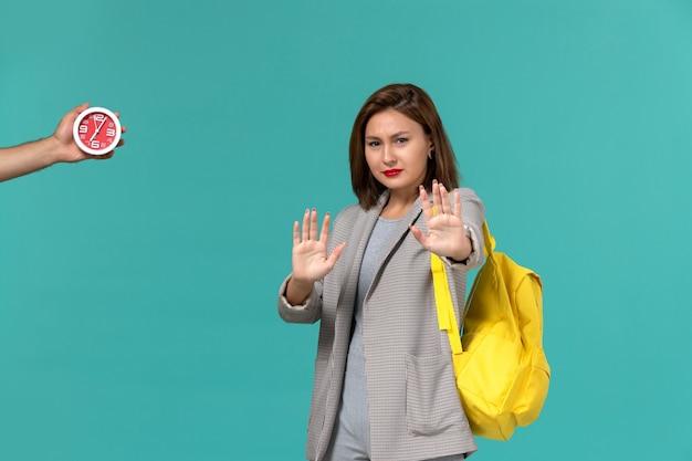 Vista frontal de uma aluna com uma jaqueta cinza usando uma mochila amarela, mostrando as mãos na parede azul clara