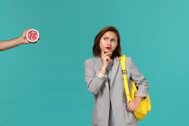 Vista frontal de uma aluna com uma jaqueta cinza usando uma mochila amarela pensando na parede azul clara