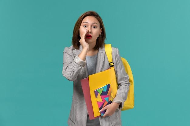 Vista frontal de uma aluna com uma jaqueta cinza usando uma mochila amarela segurando arquivos e um caderno sussurrando na parede azul