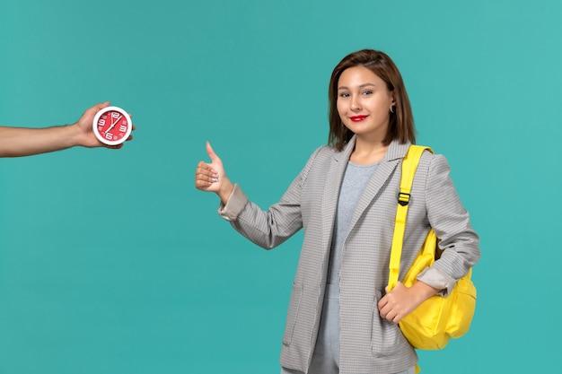 Vista frontal de uma aluna com uma jaqueta cinza usando uma mochila amarela, sorrindo na parede azul clara