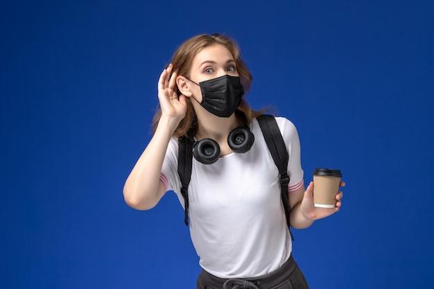 Vista frontal de uma aluna de camisa branca usando uma máscara de mochila preta e segurando um café tentando ouvir na parede azul