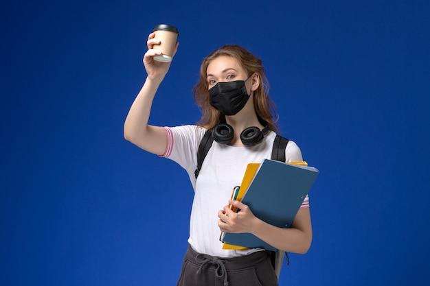 Vista frontal de uma aluna de camisa branca usando uma máscara de mochila preta segurando café e arquivos na parede azul