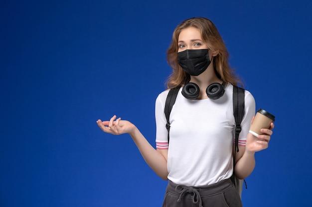 Vista frontal de uma aluna de camisa branca usando uma máscara preta de mochila e segurando um café na parede azul