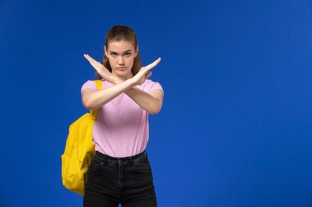 Vista frontal de uma aluna em uma camiseta rosa com mochila amarela exibindo sinal de proibição na parede azul