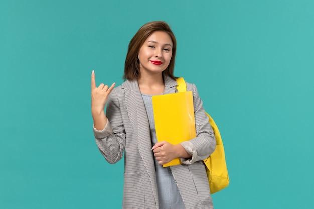Vista frontal de uma aluna em uma jaqueta cinza, usando sua mochila amarela e segurando arquivos na parede azul claro