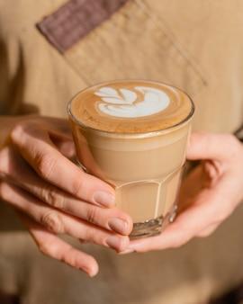 Vista frontal de uma barista com avental segurando um copo de café decorado