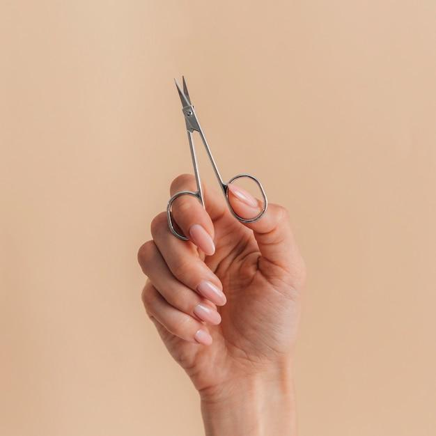 Vista frontal de uma bela manicure e tesoura saudável